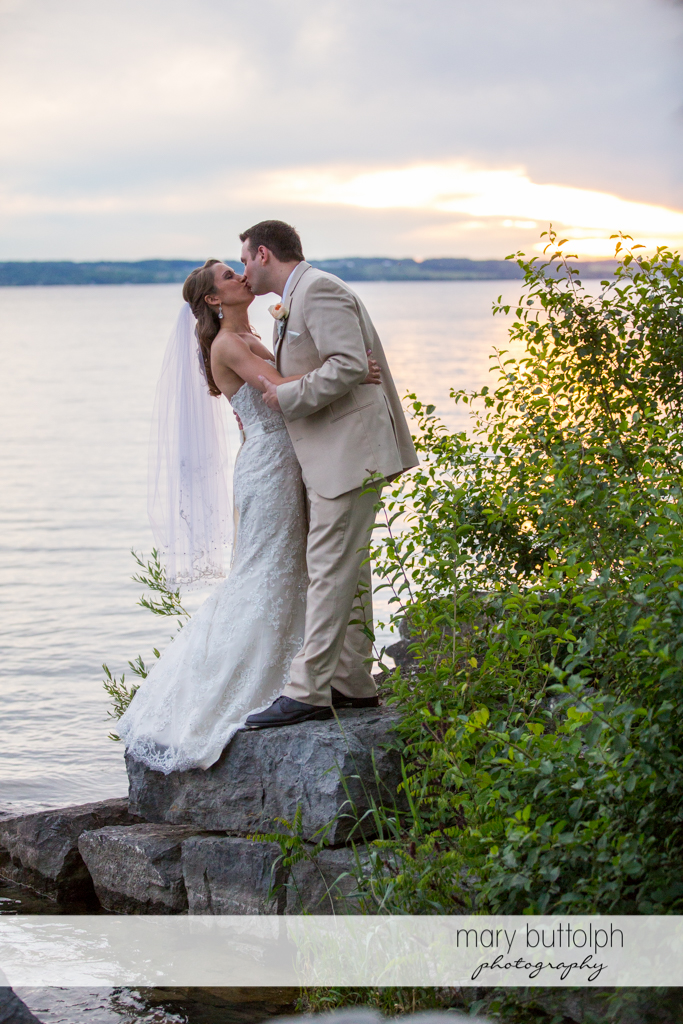 Couple kiss by the lake at the Inns of Aurora Wedding