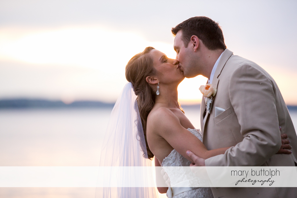 Medium shot of kissing couple by the lake at the Inns of Aurora Wedding