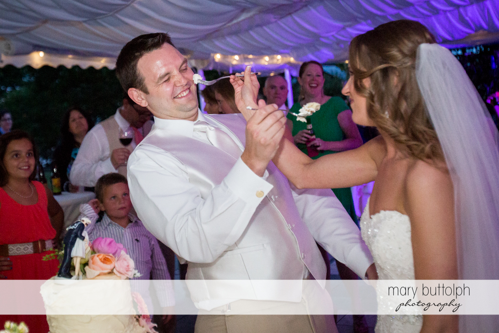Couple try their wedding cake at the Inns of Aurora Wedding