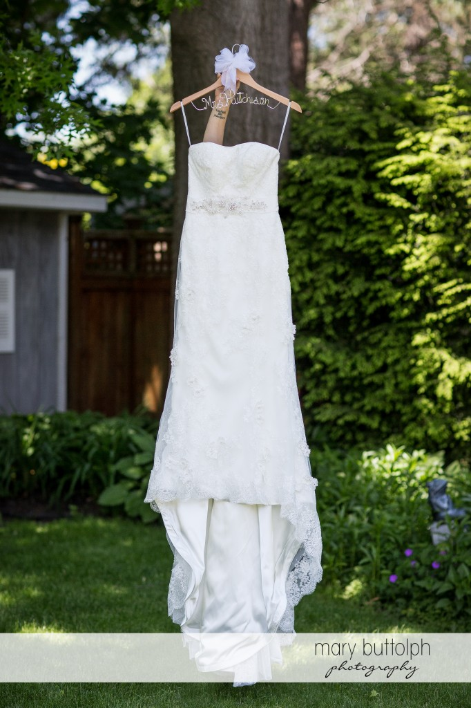 Bride's wedding dress hangs from a tree at Emerson Park Pavilion Wedding
