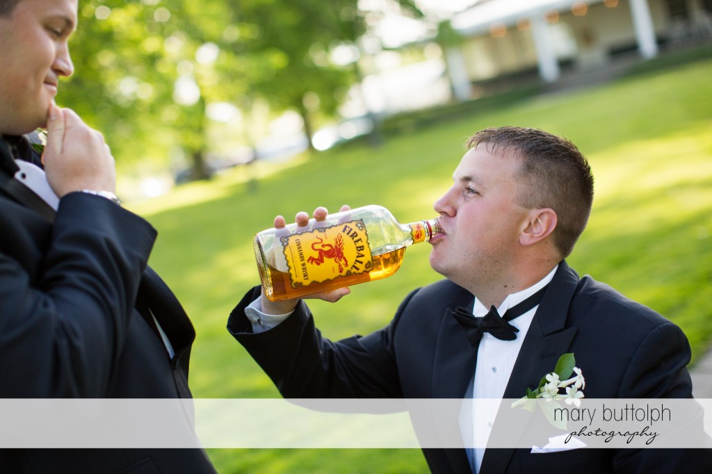 Groom looks at a groomsman drinking Fireball Cinnamon Whisky at Emerson Park Pavilion Wedding