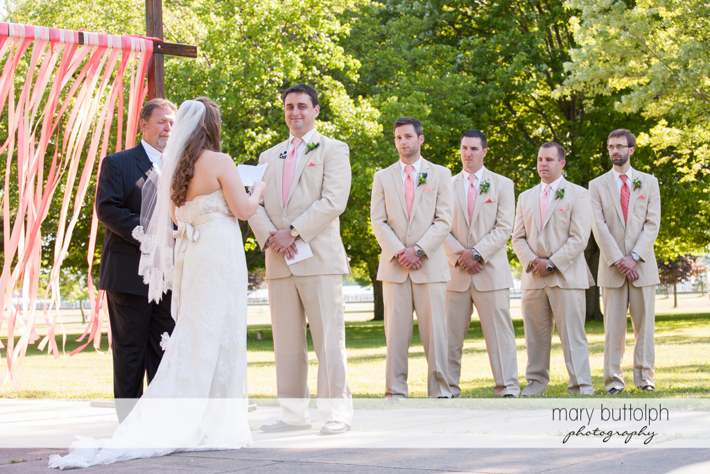 The bride faces the groom and his groomsmen at Emerson Park Pavilion Wedding
