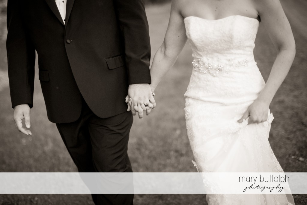 Medium shot of the couple holding hands while strolling in the garden at Emerson Park Pavilion Wedding