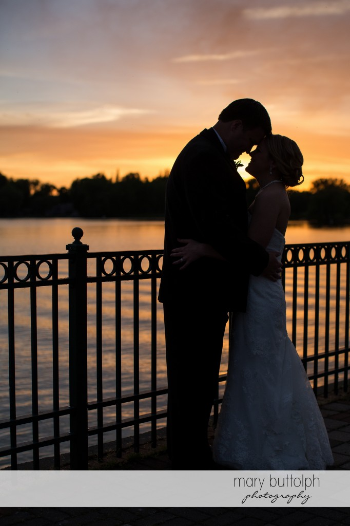Couple rub noses as the sun sets on the lake at Emerson Park Pavilion Wedding
