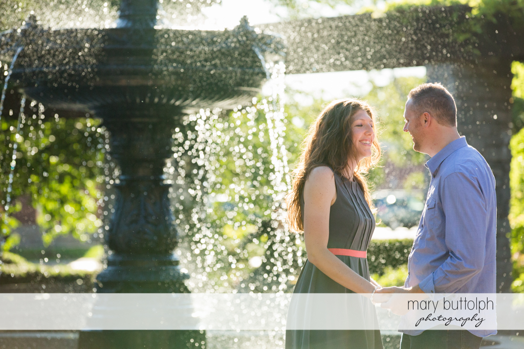 Couple pose by the fountain at Franklin Square Engagement