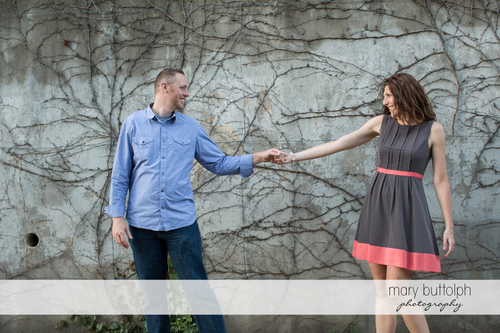 Couple in a playful mood near a concrete wall at Franklin Square Engagement