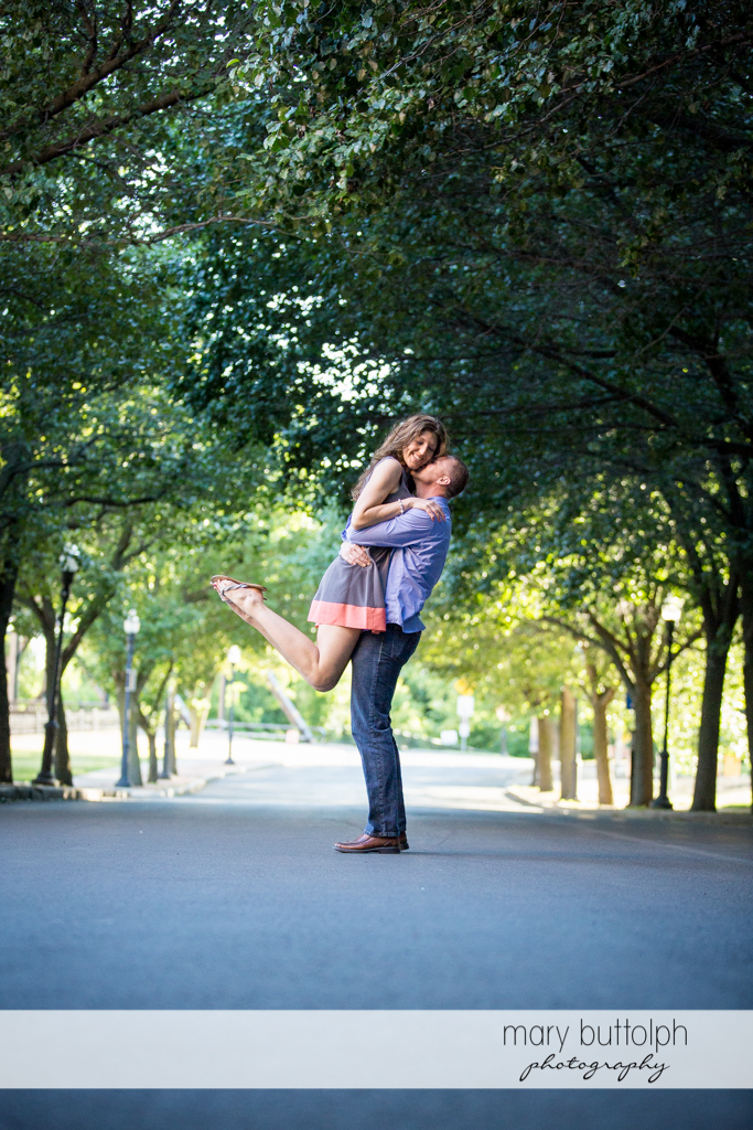 Man lifts girl to give her a kiss in the middle of the street at Franklin Square Engagement