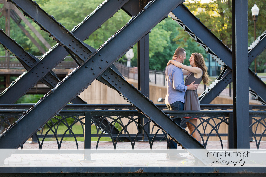 Couple embrace in the middle of a steel bridge at Franklin Square Engagement