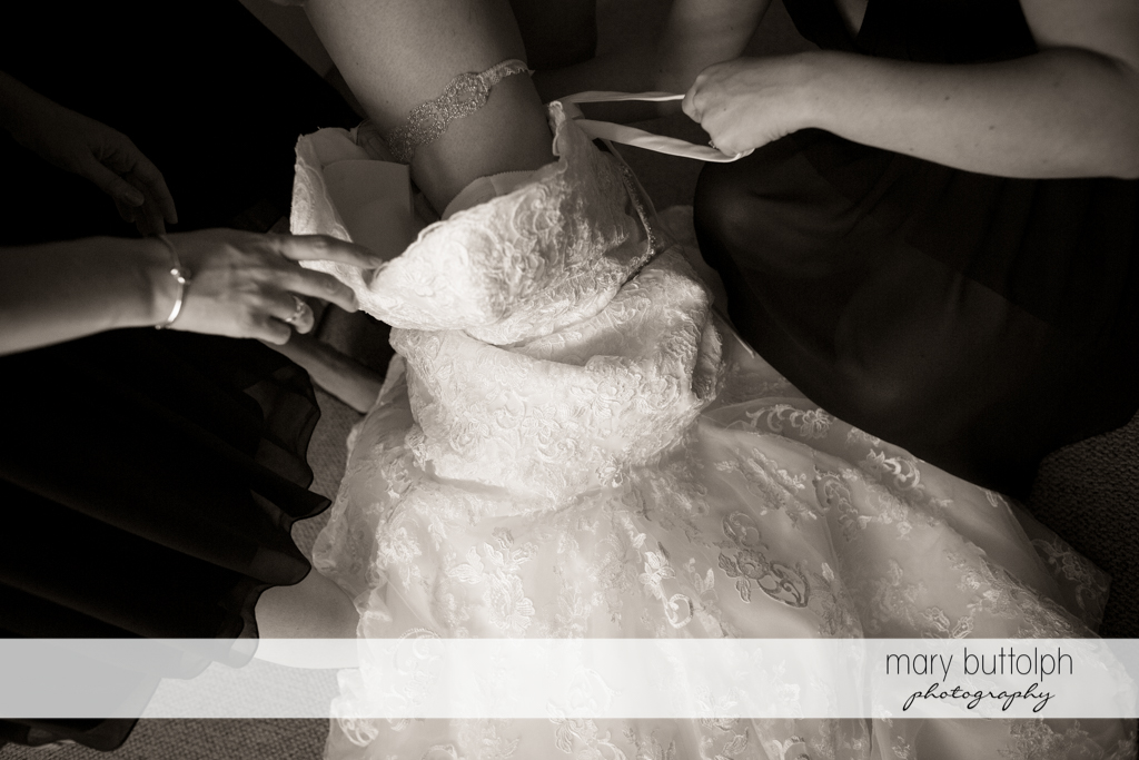 Close up shot of the bride's wedding gown being fixed by friends at the Inns of Aurora Wedding