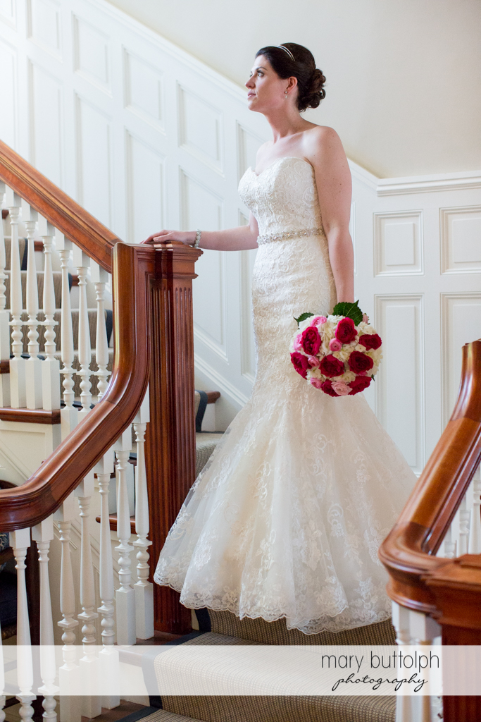 Bride with bouquet goes downstairs to meet the groom at the Inns of Aurora Wedding