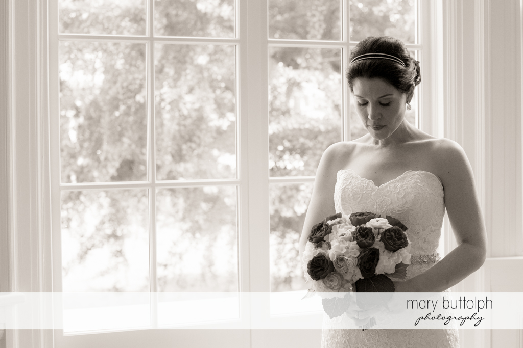 Bride with bouquet poses by the window at the Inns of Aurora Wedding