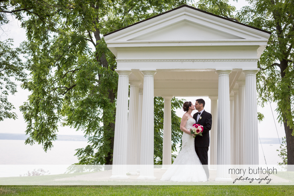 Couple rubs noses near the lake at the Inns of Aurora Wedding