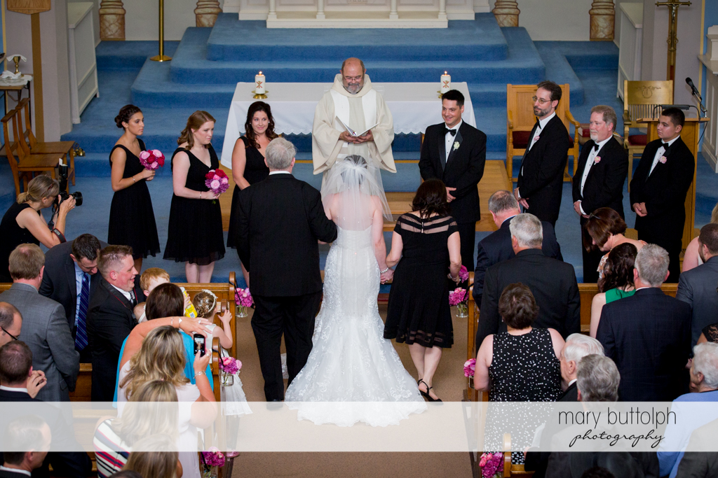 The bride and her parents reach the altar as guests look on at the Inns of Aurora Wedding