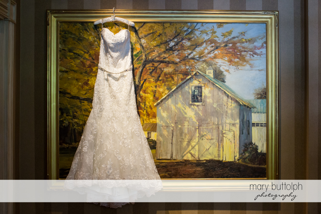 Bride's wedding dress hangs from a painting of an old barn at the Inns of Aurora Wedding