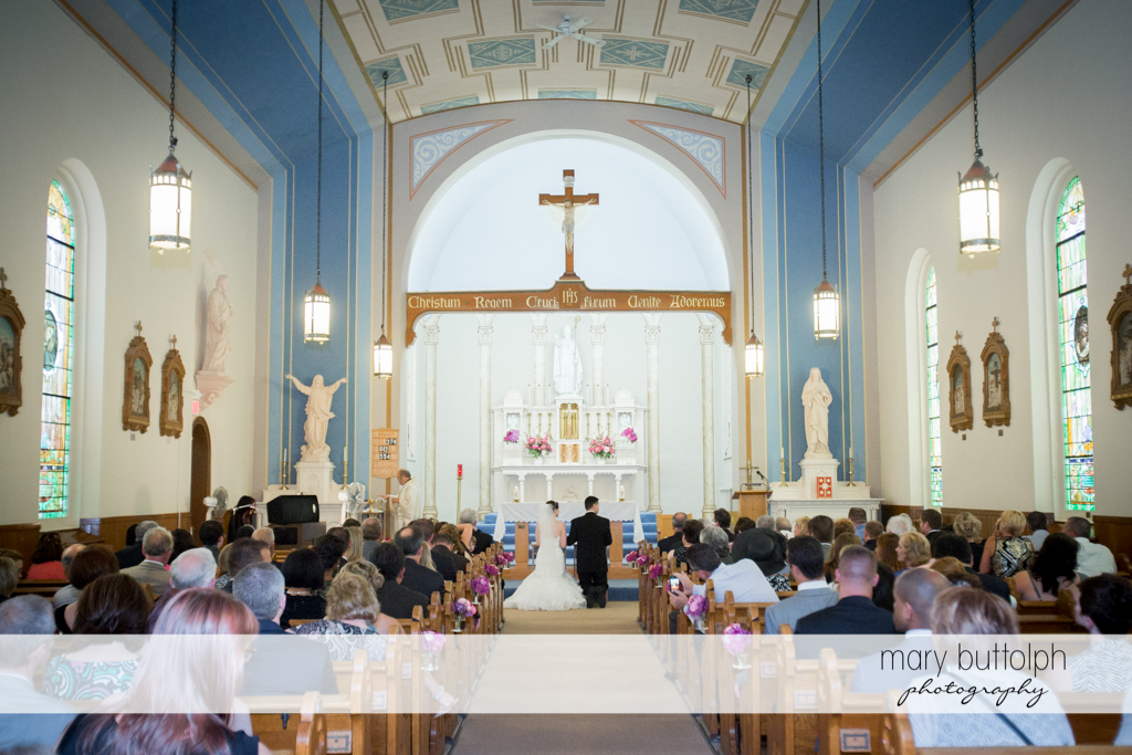 Long shot of the couple and guests in church at the Inns of Aurora Wedding