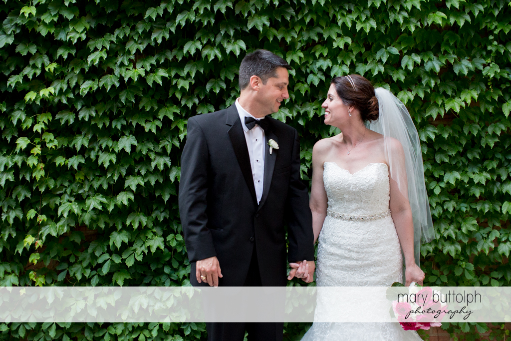 Couple hold hands in front of a wall of plants at the Inns of Aurora Wedding