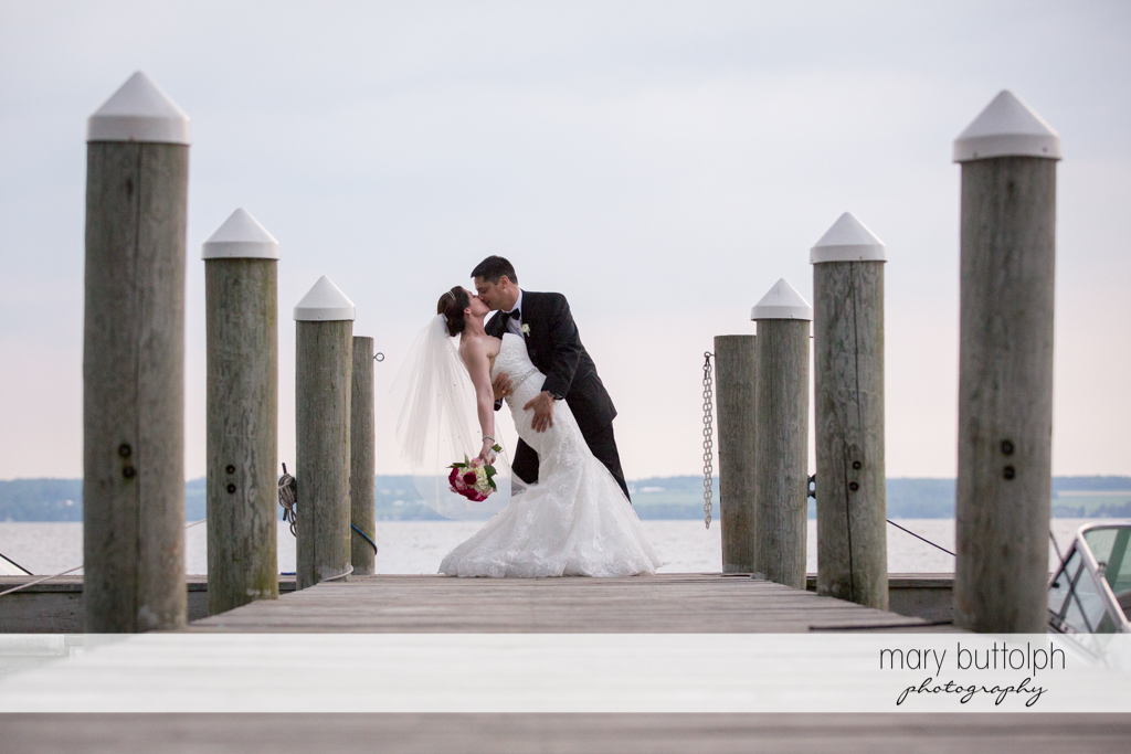 Couple kiss on the docks at the Inns of Aurora Wedding