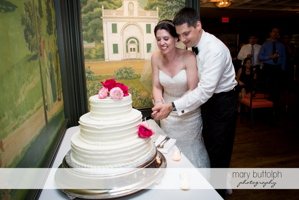 Couple slice their wedding cake at the Inns of Aurora Wedding