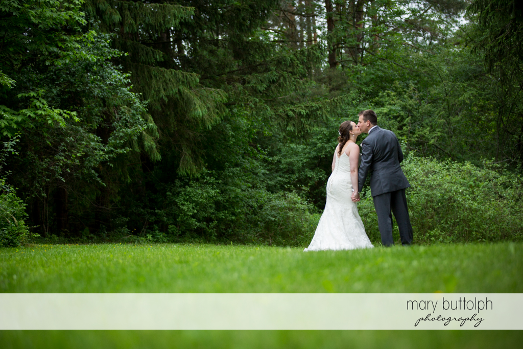 Couple kiss in the woods at the Mirbeau Inn & Spa Wedding