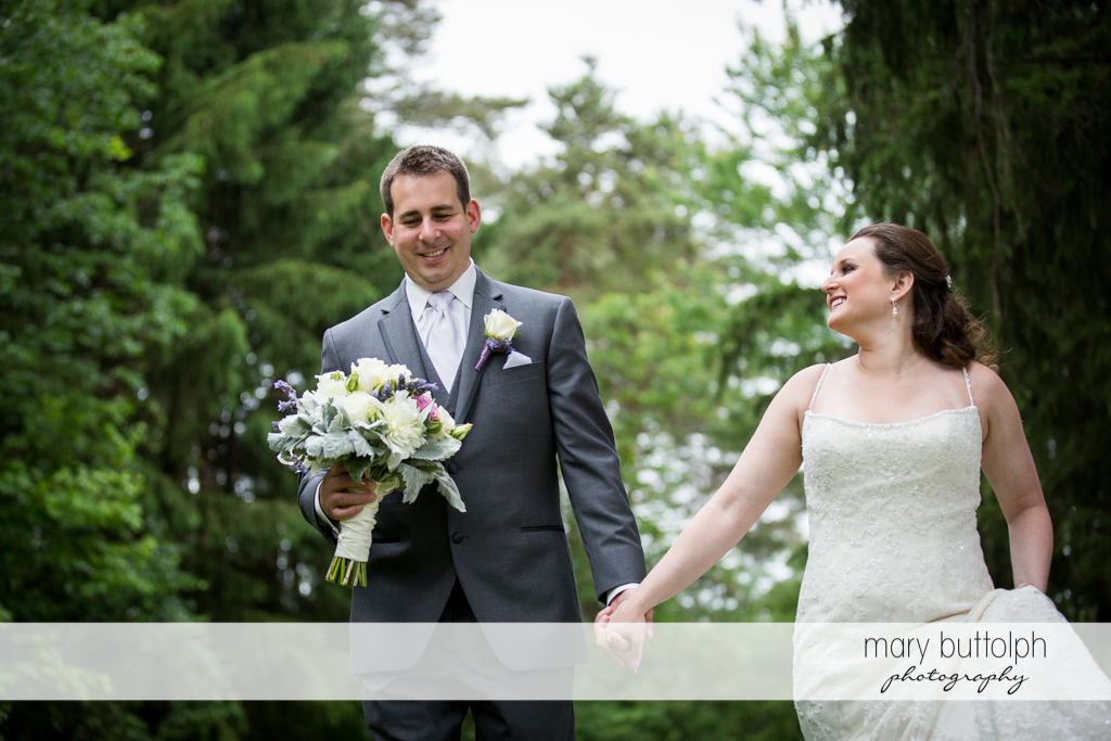 Couple stroll in the woods at the Mirbeau Inn & Spa Wedding