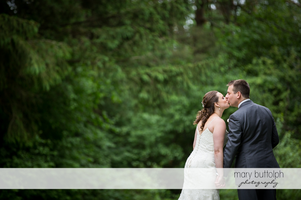 Couple in a romantic mood in the woods at the Mirbeau Inn & Spa Wedding