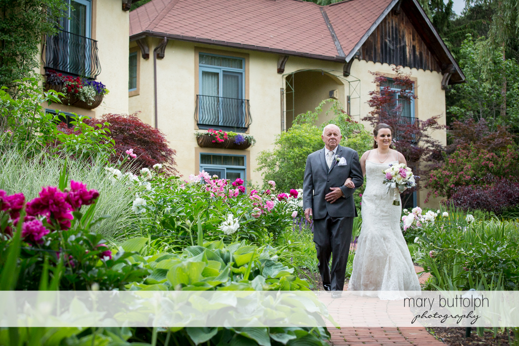 Bride is escorted by her father to the wedding venue at the Mirbeau Inn & Spa Wedding