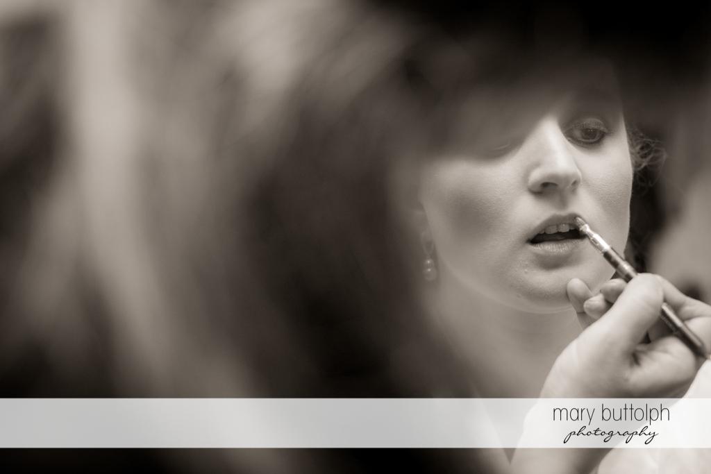 Bride uses lip gloss at the Mirbeau Inn & Spa Wedding