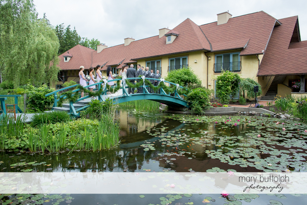 Another long shot of the wedding party on the wooden bridge at the Mirbeau Inn & Spa Wedding