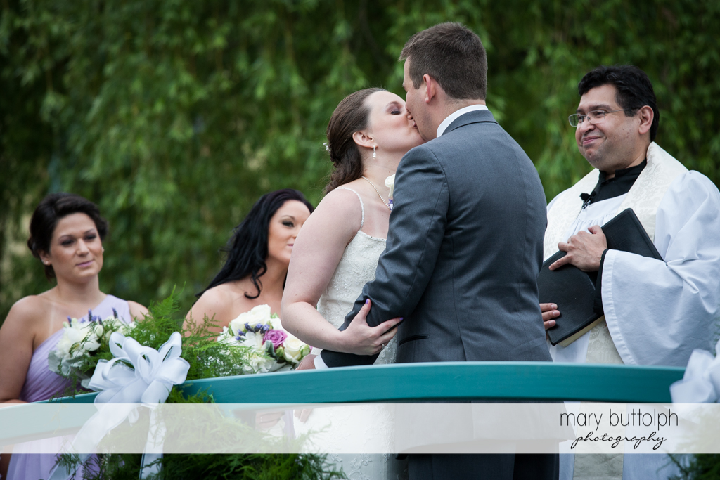 Couple kiss in front of the priest at the Mirbeau Inn & Spa Wedding