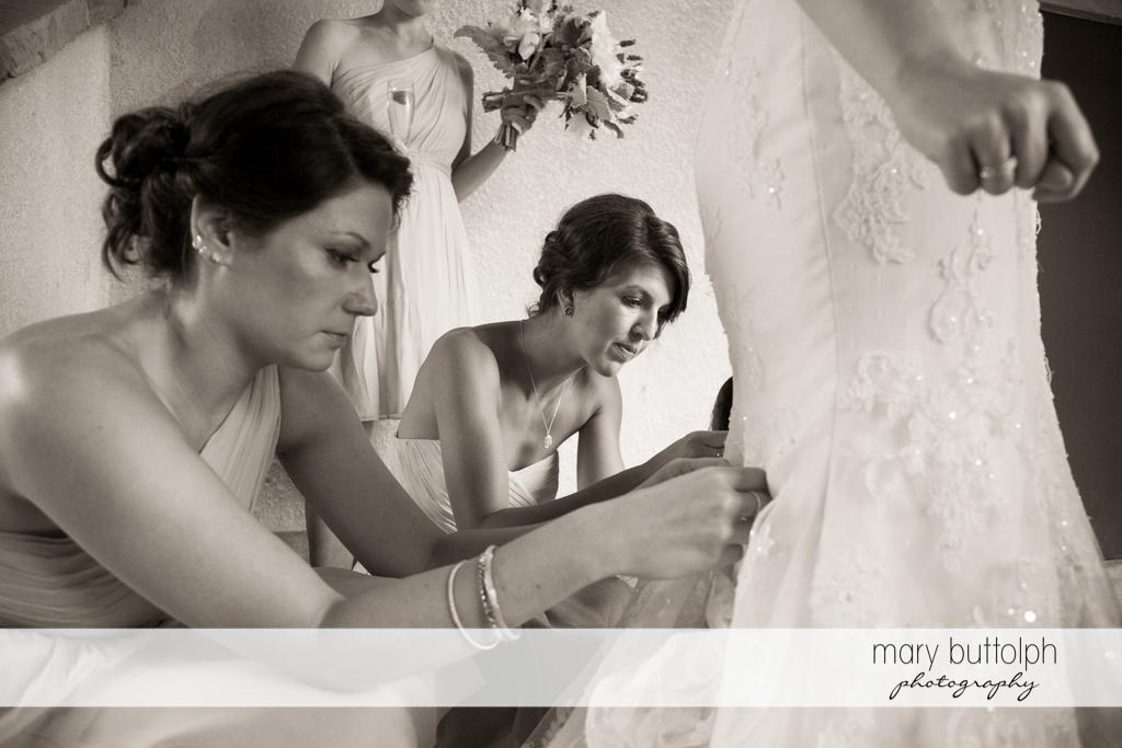 Bridesmaids busy fixing the bride's wedding dress at the Mirbeau Inn & Spa Wedding
