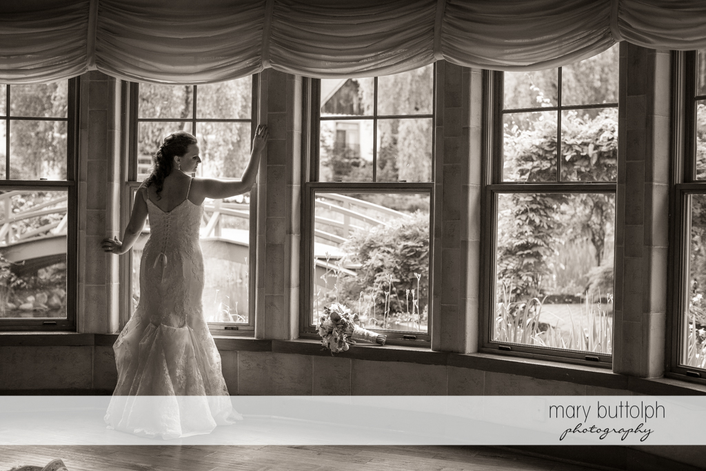 Back view of the bride standing by the window at the Mirbeau Inn & Spa Wedding