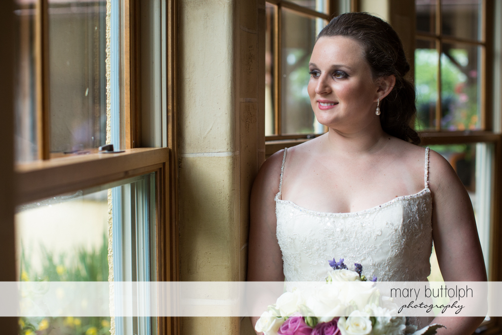 Bride with bouquet by the window at the Mirbeau Inn & Spa Wedding
