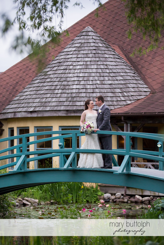 Couple on the wooden bridge in front of the inn at the Mirbeau Inn & Spa Wedding
