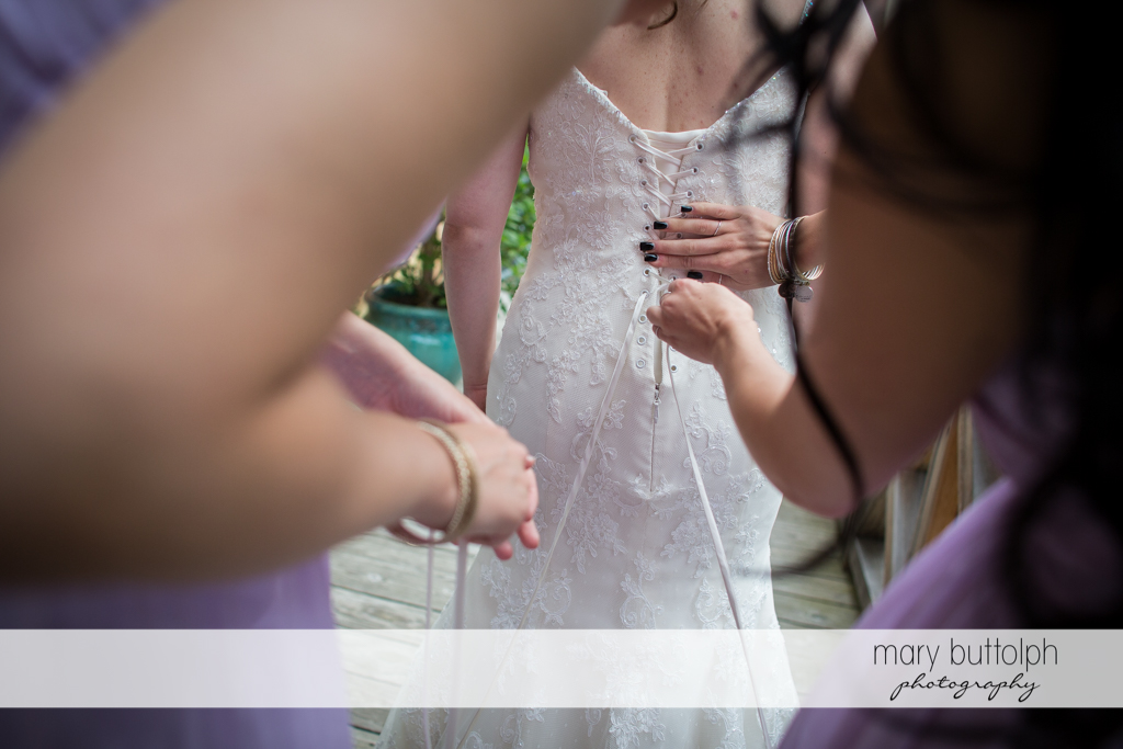Bride's wedding dress is adjusted by bridesmaids at the Mirbeau Inn & Spa Wedding