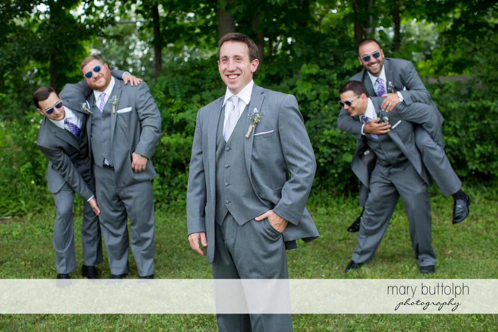 The groom and his groomsmen clown around in the garden at the Sherwood Inn Wedding