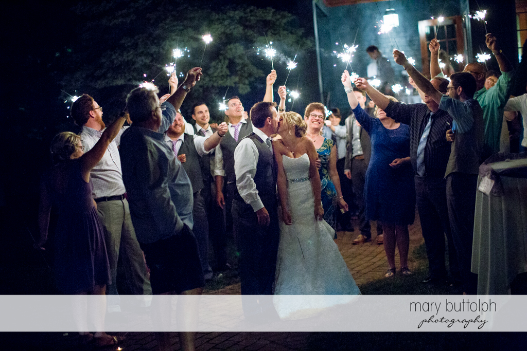 Couple kiss as guests hold up sparklers at the Sherwood Inn Wedding