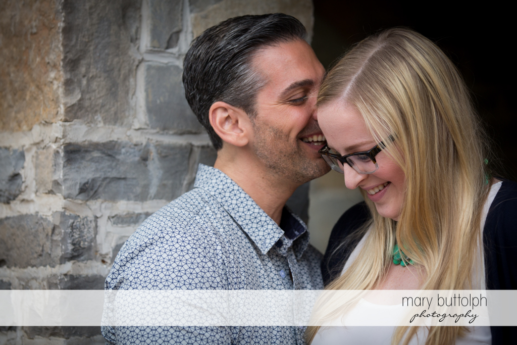 Couple can't hide their joy as they pose in front of a brick wall at Skaneateles Engagement