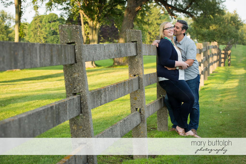 Couple spend time together near a fence in the garden at Skaneateles Engagement