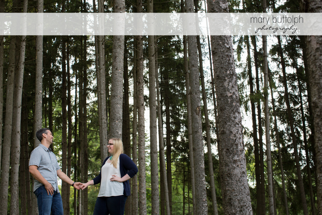 Couple hold hands near the trees at Skaneateles Engagement
