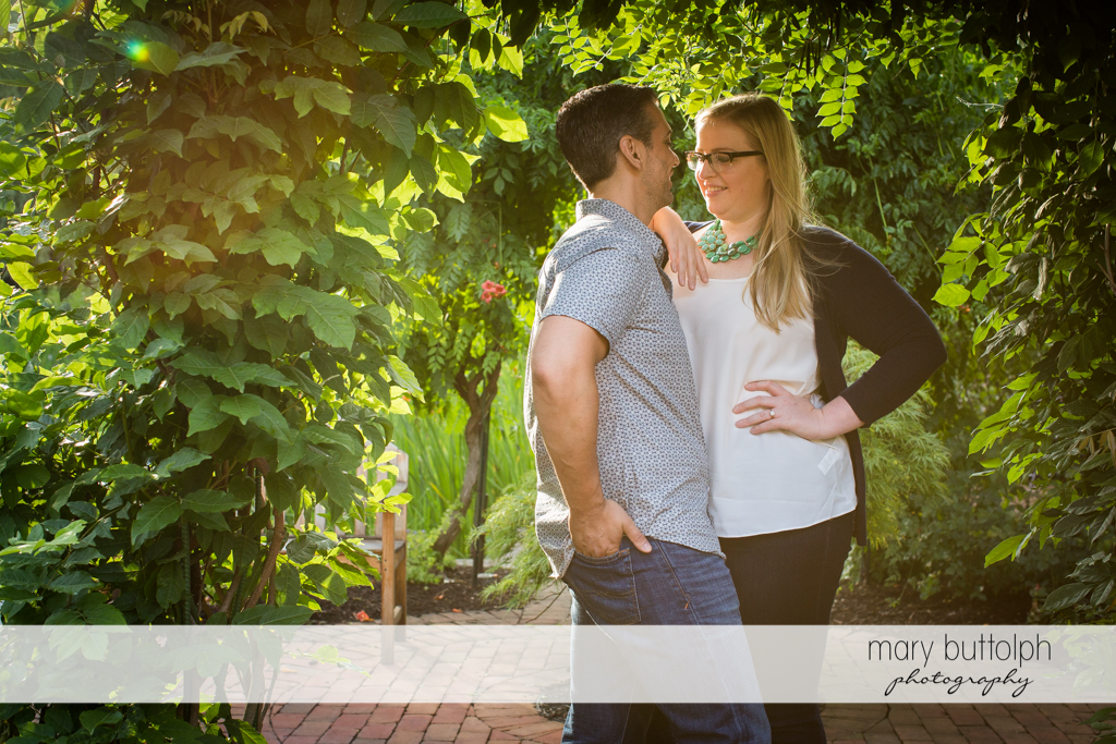 Couple share a quiet moment in the garden at Skaneateles Engagement