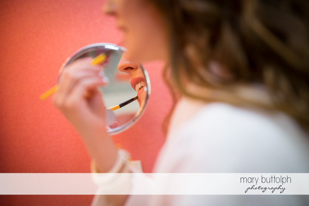 Bride's reflection appears in the mirror at the Inns of Aurora Wedding