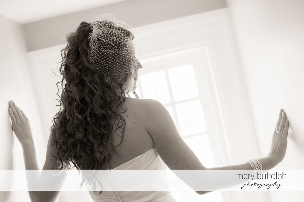 Veiled bride poses in front of the window at the Inns of Aurora Wedding