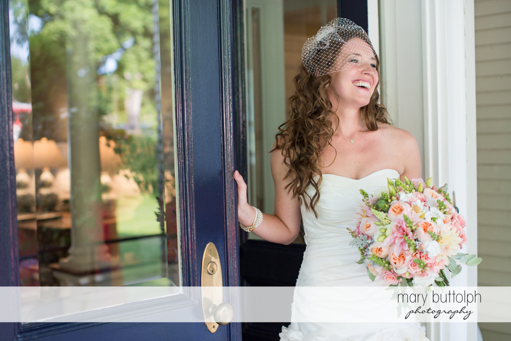 Smiling bride with bouquet at the doorway at the Inns of Aurora Wedding