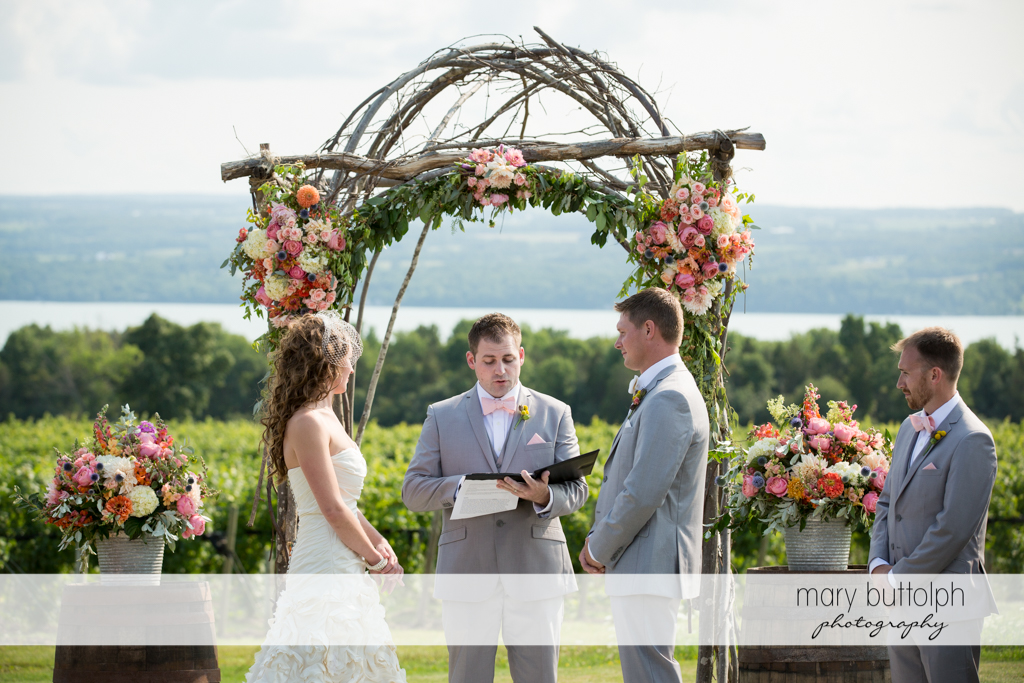 Couple face the wedding officiant in the garden at the Inns of Aurora Wedding