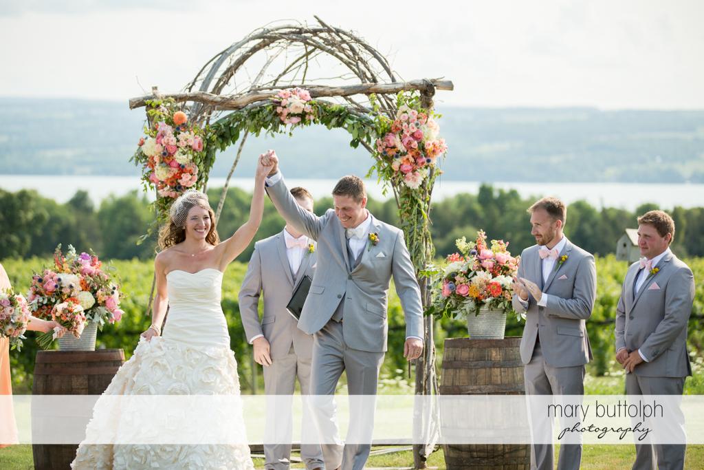 Couple raise their hands in the garden at the Inns of Aurora Wedding