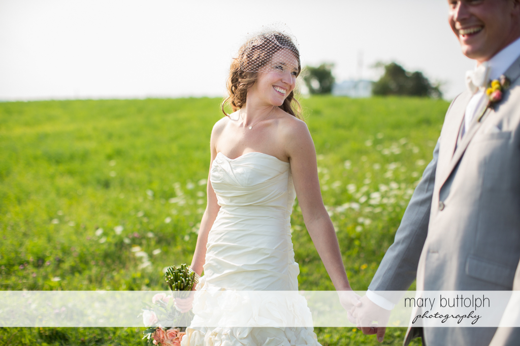 Couple hold hands in the garden at the Inns of Aurora Inn Wedding