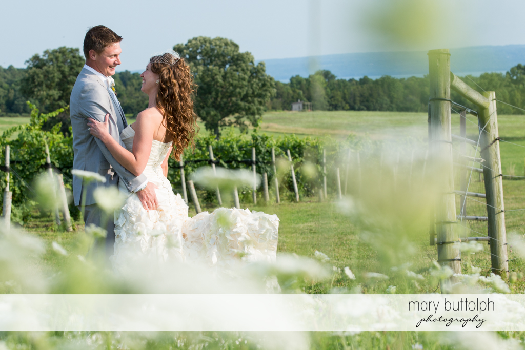 Couple embrace in the vineyard at the Inns of Aurora Wedding