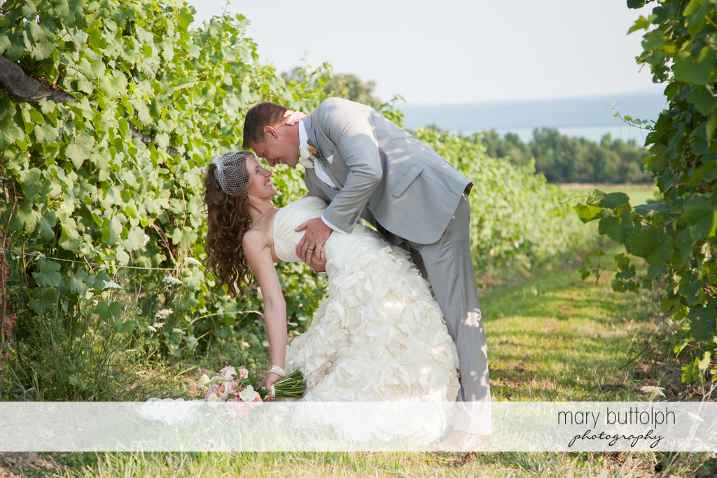 Couple pose for the camera in the vineyard at the Inns of Aurora Wedding