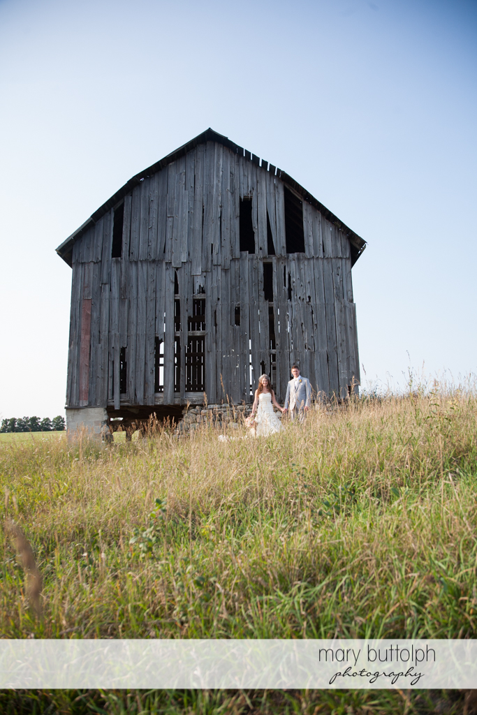 Couple stand in front of an old barn at the Inns of Aurora Wedding