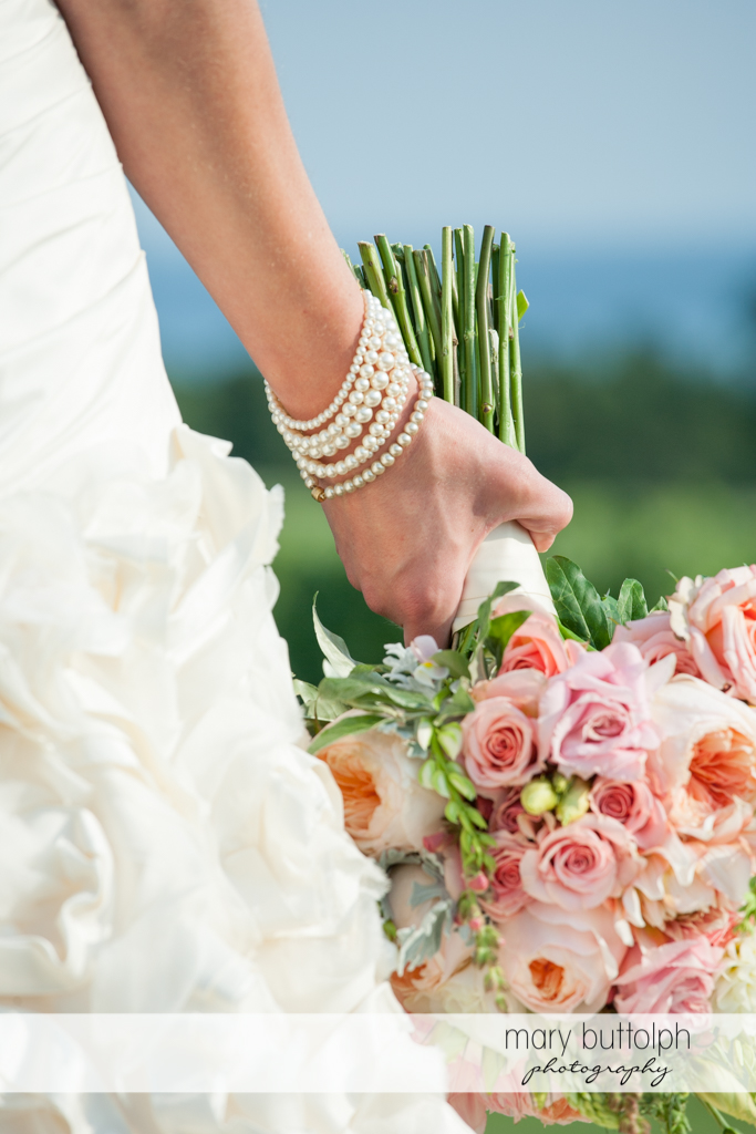 Close up shot of the bride's pearl bracelets and bouquet at the Inns of Aurora Wedding